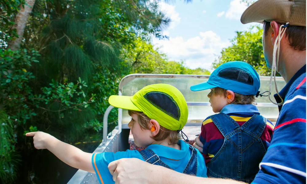 family taking boat ride through everglades swamp in florida