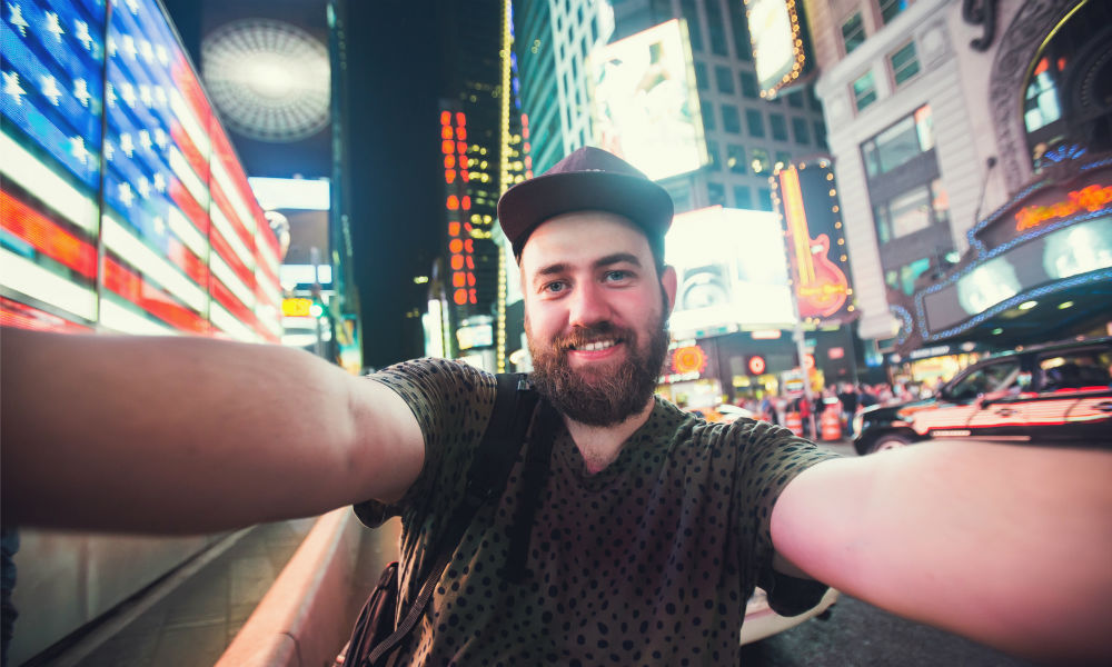 bearded man backpacker smiling and taking selfie photo on Times Square in New York