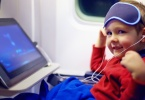 little boy on airplane with sleep mask on