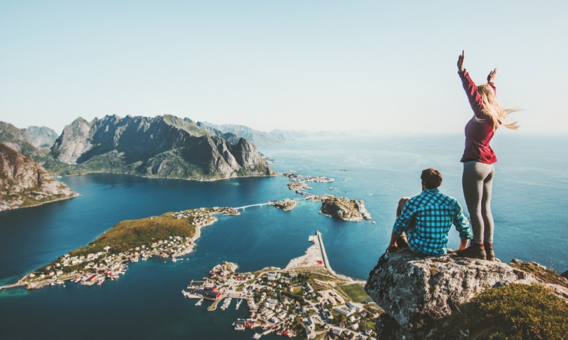 Couple travelers traveling together on top cliff Reinebringen mountain in Norway