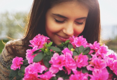 young woman smelling pink flowers