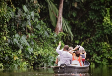 The tour guide shows tourists in a canoe the beauty of the nature at a river in the Tortugero National Park, Costa Rica