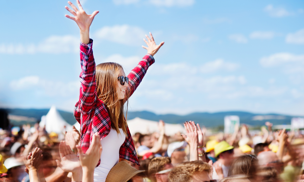 girl on someone's shoulders at music festival